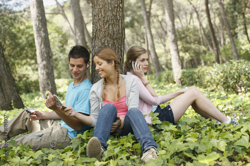 Friends using technology in forest