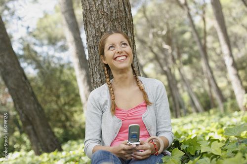 Girl text messaging in forest