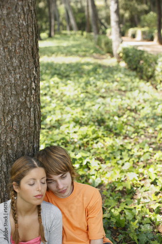 Couple leaning against tree in forest