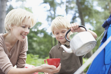Boy pouring hot water for mother at campsite