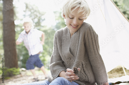 Woman looking at pine cone in woods