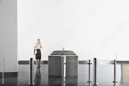 Businesswoman using cell phone near turnstile