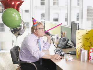 Businessman having birthday party at desk