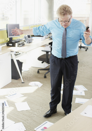 Businessman looking at papers on floor