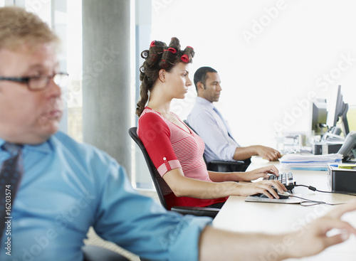 Businesswoman working and wearing curlers at desk