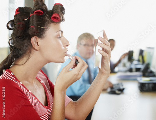 Businesswoman in curlers applying lipstick at desk