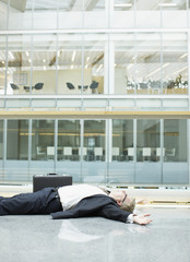 Businessman unconscious in building lobby