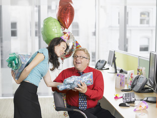 Businesswoman giving birthday gift to co-worker