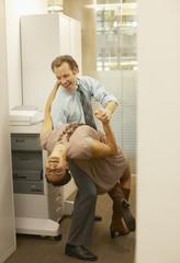 Businesspeople dancing in copy room