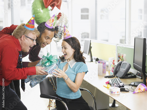Businessmen giving birthday gift to co-worker