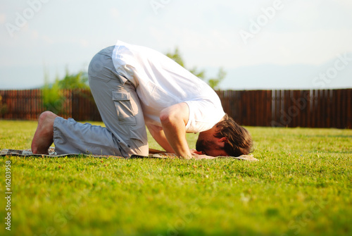 Muslim male is praying outdoor on green ground