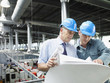 Businessmen looking at blueprints in factory
