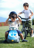 Childhood activity with truck toy and bike on green meadow poster