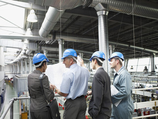 Businesspeople in hard-hats looking at blueprints