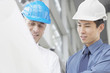 Businessmen in hard-hats looking at blueprints