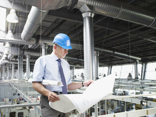 Businessman in hard-hat looking at blueprints