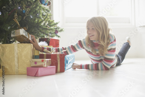 Girl looking at Christmas gifts under tree
