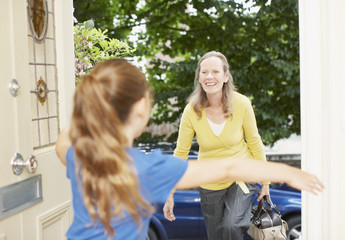 Daughter greeting mother at front door