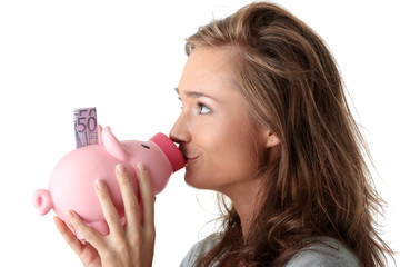 Young beautiful woman standing with piggy bank