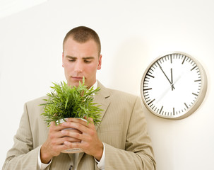 businessman holding a plant