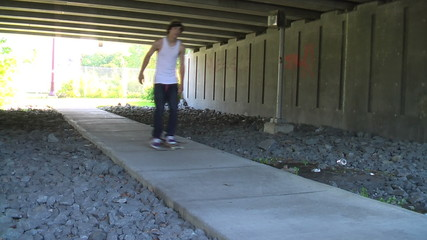 Skateboarder rolling by on path