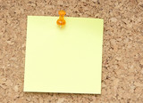green reminder note with orange pin on corkboard poster