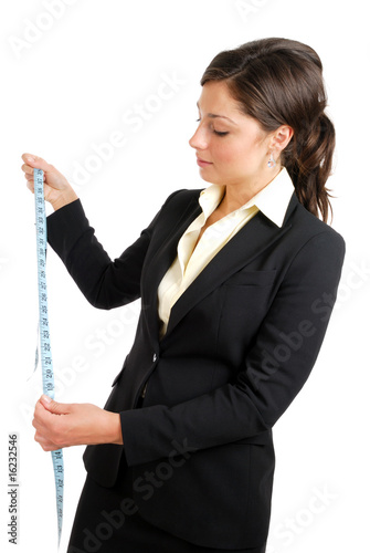Business woman looking at a measuring tape