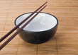 Chopsticks with  ceramic bowl on bamboo mat
