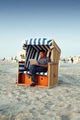 Geschäftsmann am Strand mit Laptop arbeitend