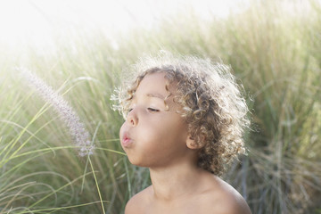 Boy blowing grass seeds