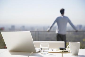 Man taking a break from working on balcony