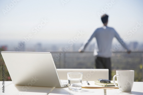 Man taking a break from working on balcony