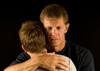 Father cries as he hugs his son