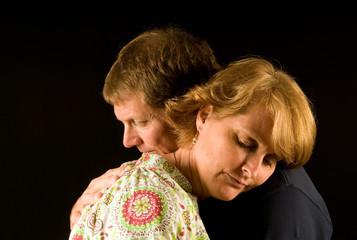 Husband and wife have a sorrowful hug
