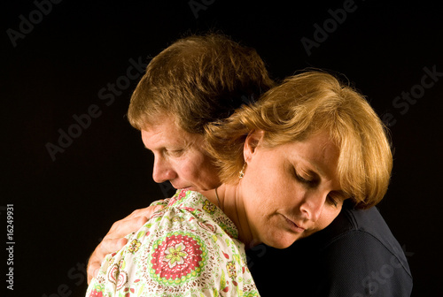 Husband and wife have a sorrowful hug
