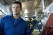 Technician posing in auto shop