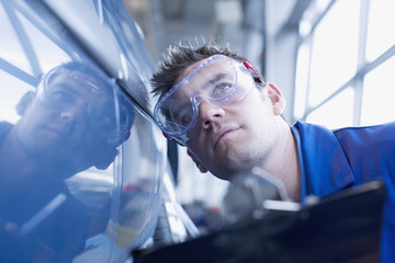 Technician inspecting car