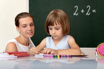 Elementary school pupil working under with teacher