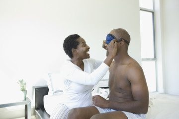 Woman placing sleeping mask on husband