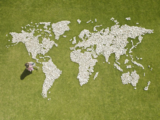 Girl watering world map made of rocks