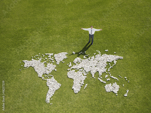 Businessman standing near world map made of rocks
