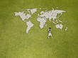 Boy using laptop near world map made of rocks