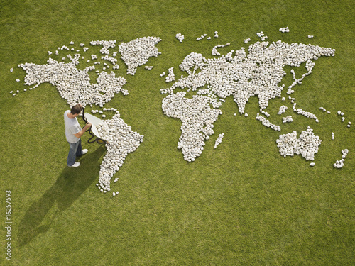 Man making world map made of rocks