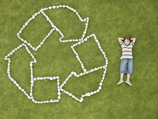 Boy relaxing near recycling symbol made of rocks