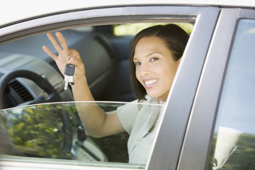 Woman sitting in car holding car keys