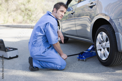 Mechanic changing car?s flat tire