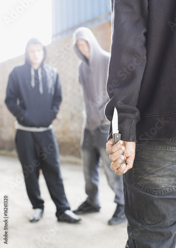 Two men being confronted by man with knife
