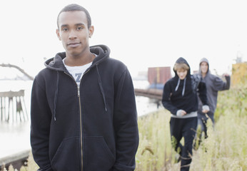Three young men walking through urban field