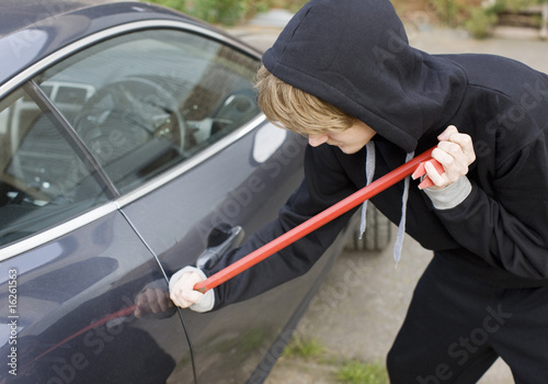 Burglar prying car window open with crowbar