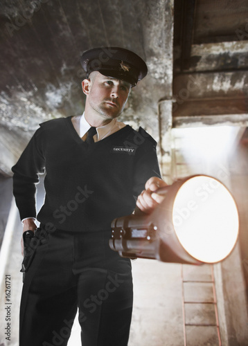 Security guard shining flashlight into bunker